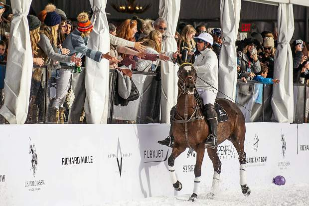 Nacho Figueras high fives fans in the VIP area at the St. Regis snow polo tournament at Rio Grande Park in Aspen on Wednesday afternoon.