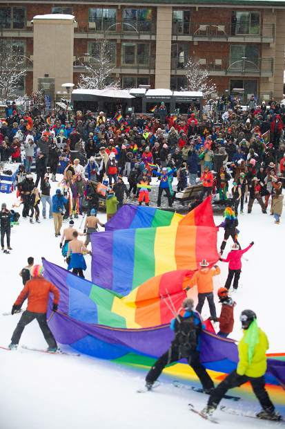 An enormous rainbow flag gets skied down to the base of Aspen Mountain for the annual Gay Ski Week costume downhill competition on Friday.
