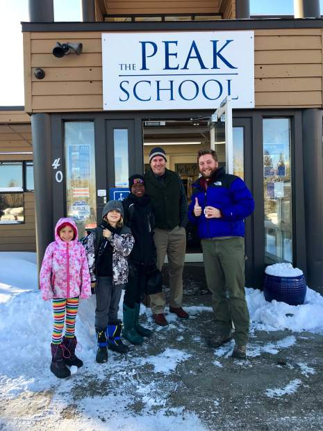 Jonas and the Ohayon family stand outside The Peak School with Travis Aldrich and Luke Wander.