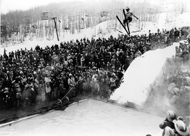 A man on skis goes off a ramp into a swimming pool during Wintersköl Ski Splash as a large crowd looks on.