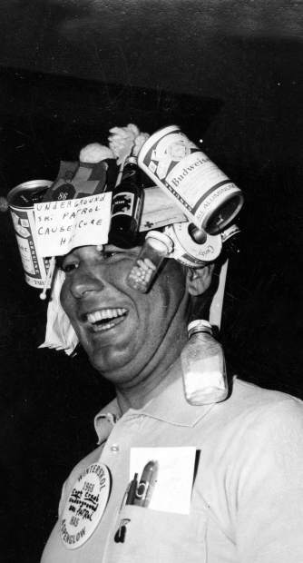 Mal Kolpak wears a hat with beer cans, pill, and bottles at the mad Hatters ball during the 1968 Wintersköl. A sign on his hat says