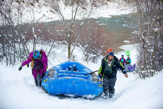 Rafters walk their boat up the Grizzly Creek takeout after completing the Shoshone section of the Colorado River in Glenwood Springs for the annual paddle event on New Year's Day.