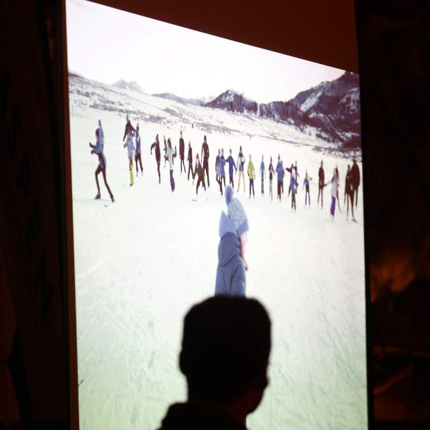 Development director Miah Wheeler watches a short video during the Aspen Valley Ski and Snowboard Club hall of fame dinner at the T-Lazy-7 Ranch on Saturday, Feb. 23, 2019. (Photo by Austin Colbert/The Aspen Times).