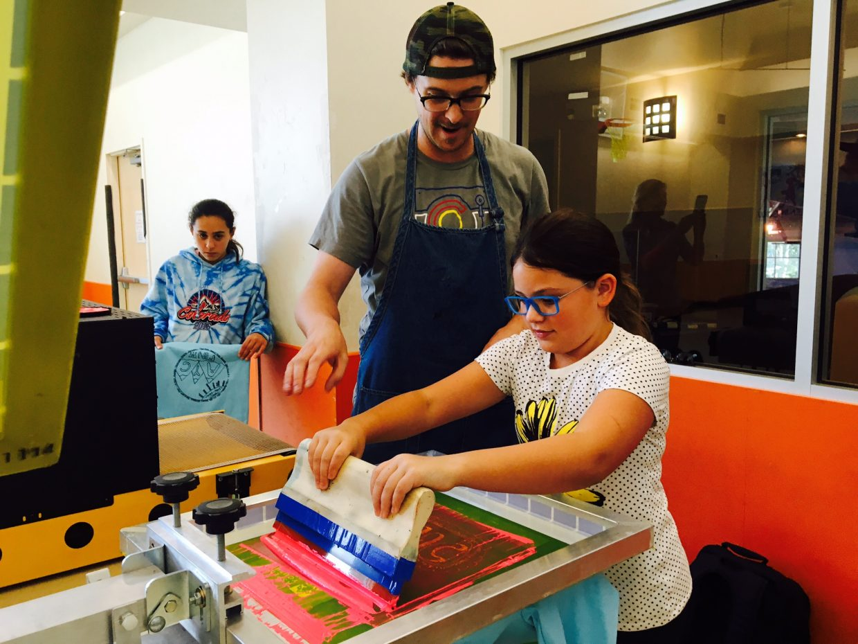 Bo Gallagher from Zappazoo Inkworks shows an AYC kid how to screen print