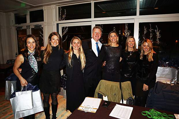 Event auctioneer Christian Kolberg surrounded by Aspen Event Works' star-studded staff.
