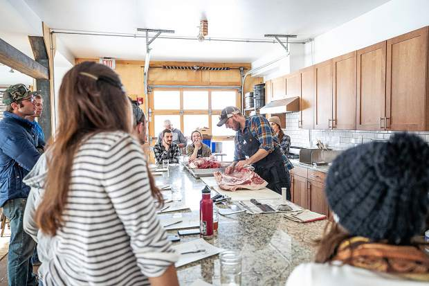 Rock Bottom Ranch Director Jason Smith demonstrates Tuesday how to butcher a pig. Watching are employees of local restaurants, independent chefs, grocers and farm-to-market shops.