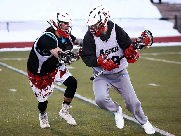 Aspen High School players run through drills during boys lacrosse practice on Tuesday, Feb. 26, 2019, on the AHS turf.