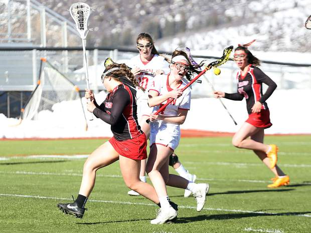 Aspen High School junior Charlotte Howie tries to keep hold of the ball during a girls lacrosse game against Durango on Tuesday, March 19, 2019, on the AHS turf. (Photo by Austin Colbert/The Aspen Times).