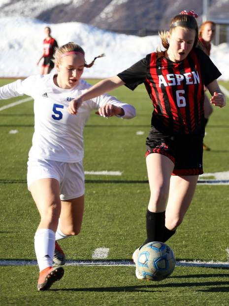 Aspen High School's Payton Curley, right, battles with Roaring Fork's Lucia Penzel duirng a girls soccer game on Tuesday, March 19, 2019, on the AHS turf. (Photo by Austin Colbert/The Aspen Times).