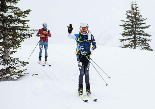 Breckenridge resident Sam O'Keefe waves to the camera as race partner, Hugh Carey, follows at the top of the first descent from Aspen Snowmass Resort during the Audi Power of Four ski mountaineering race on March 2, near Aspen. The annual ski mountaineering race brought hundreds of athletes to scale nearly 11 thousand feet of vertical climbing over the course of 25 miles, summiting all four Aspen area ski resorts.