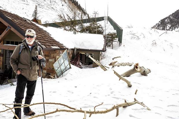 Avalanche consultant Art Mears stands outside a home on Conundrum Creek Road Tuesday that was damaged last weekend by a massive avalanche. Mears designed the splitting wedge wall on the south side of the house that likely prevented its destruction.