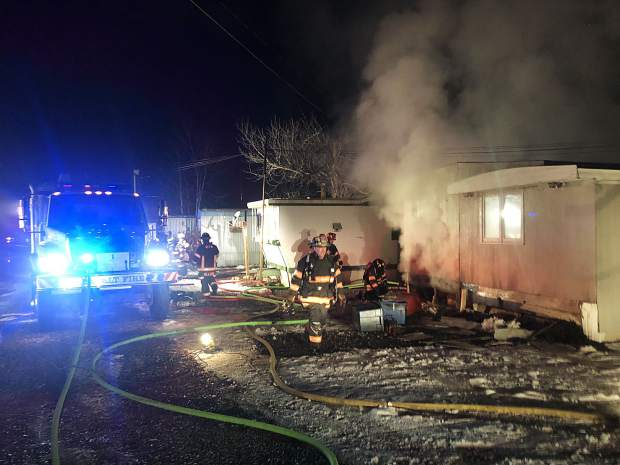 Firefighters with the Roaring Fork Fire Rescue Authority extinguish a fire at a mobile home on Homestead Drive in Basalt.