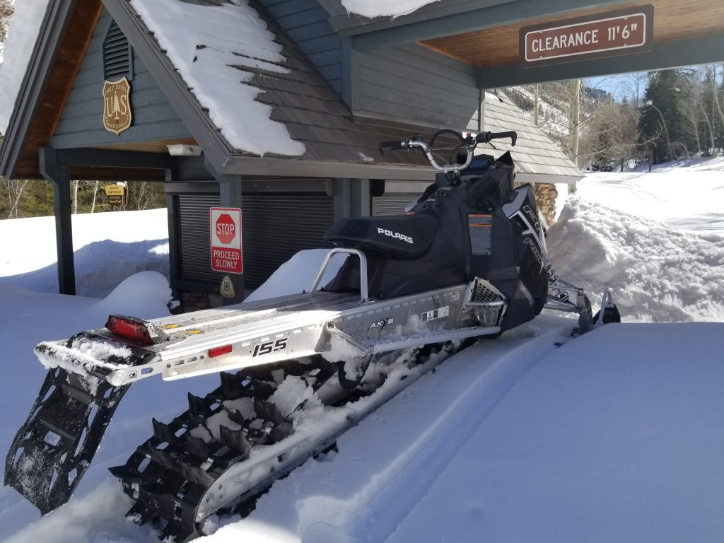 White River National Forest law enforcement officer Chris Mandrick investigated conditions in Maroon Creek Valley last weekend. His snowmobile is perched on debris deposited by one of the avalanches on the road.
