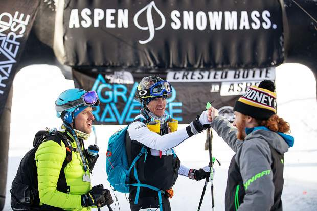 Cam Smith fist bumps Tyler Newton, center, after Newton and partner Scott Archer, left, finished the Grand Traverse race in fourth Saturday morning in Aspen. Cam Smith and his partner Rory Kelly took first overall.