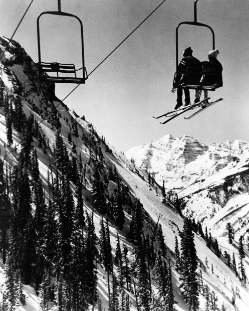 Two skiers ride the original LogesPeak Lift at Aspen Highlands in 1965. The lift provided an awesome view of the Maroon Bells, in the background.