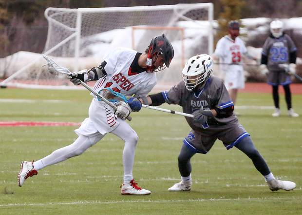 Aspen High School senior Dawson Holmes, left, goes on the attack during the boys lacrosse game against Fruita Monument on Wednesday, April 3, 2019, on the AHS turf. Fruita won, 14-9. (Photo by Austin Colbert/The Aspen Times).