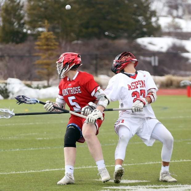 Aspen High School's Cooper Johnson, right, looks around for an airborne ball in the boys lacrosse game against Montrose on Saturday, April 6, 2019, on the AHS turf. (Photo by Austin Colbert/The Aspen Times).