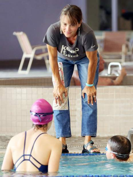 Aspen Swim Club coach Becky Jager listens to a swimmer talk during practice on April 5, 2019, at the Aspen Recreation Center pool. (Photo by Austin Colbert/The Aspen Times).