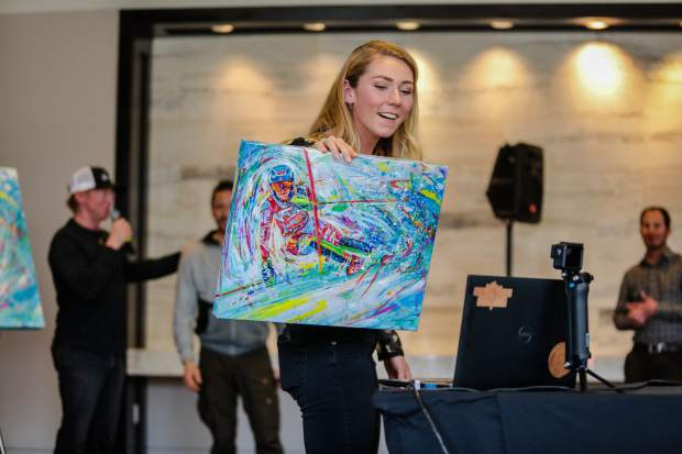 Mikaela Shiffrin shows the people watching digitally her painting artist David Gonzales commissioned for her as a gift Sunday at the Westin in Avon. Gonzales also did larger pieces to be auctioned off.