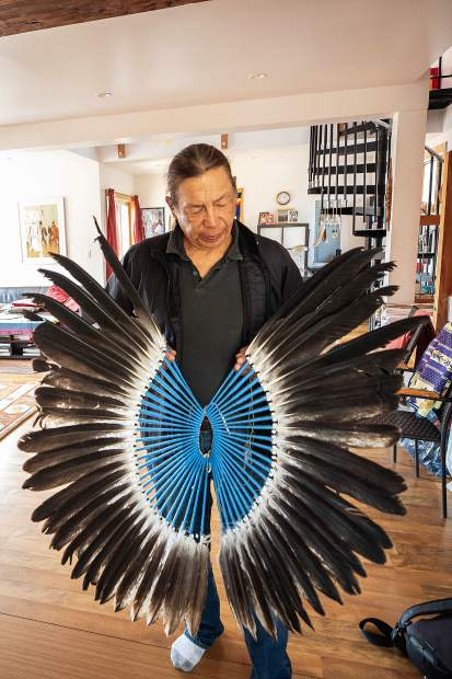 Anuk Bald Eagle holds up his regalia that he has made from eagle feathers his family has given him at his home in Woody Creek on Saturday afternoon.