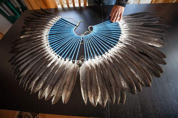 Anuk Bald Eagle spreads out his regalia that he has made from eagle feathers his family has given him on his kitchen table at his home in Woody Creek on Saturday afternoon.