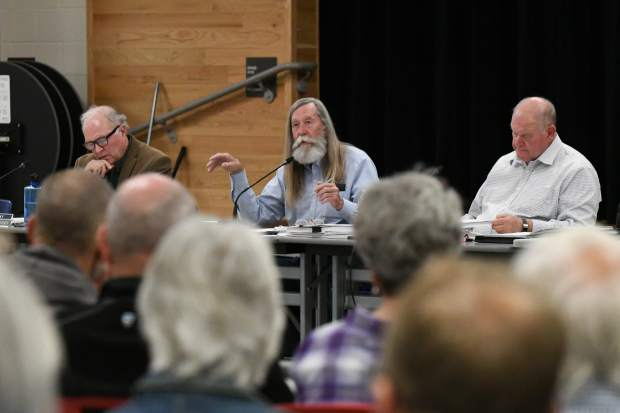 Garfield County Commissioner John Martin, seated between fellow commissioners Tom Jankovsky, left, and Mike Samson, speaks at the start of the Rocky Mountain Resources permit review public meeting held at Glenwood Springs Middle School on Monday evening.