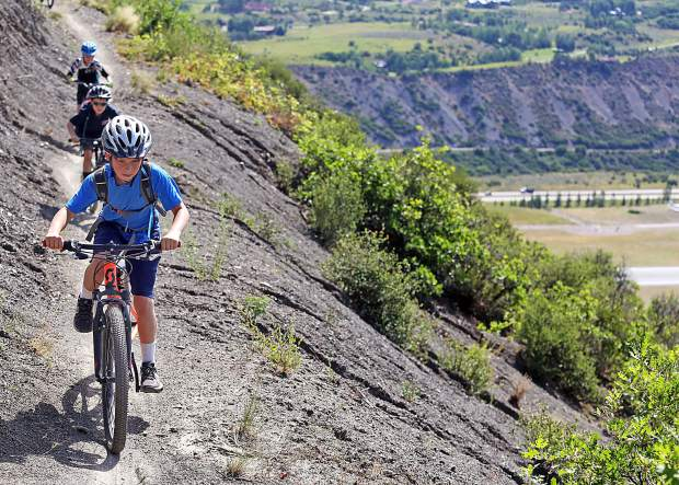 Led by instructor Jason Cook, children take part in one of the Aspen Valley Ski and Snowboard Club's mountain bike clinics around Aspen in 2017. Here they rode the Airline Trail near the airport, the second of three days dedicated to introducing the riders to the basics of mountain biking. On the final day, they rode the Rim Trail in Snowmass.