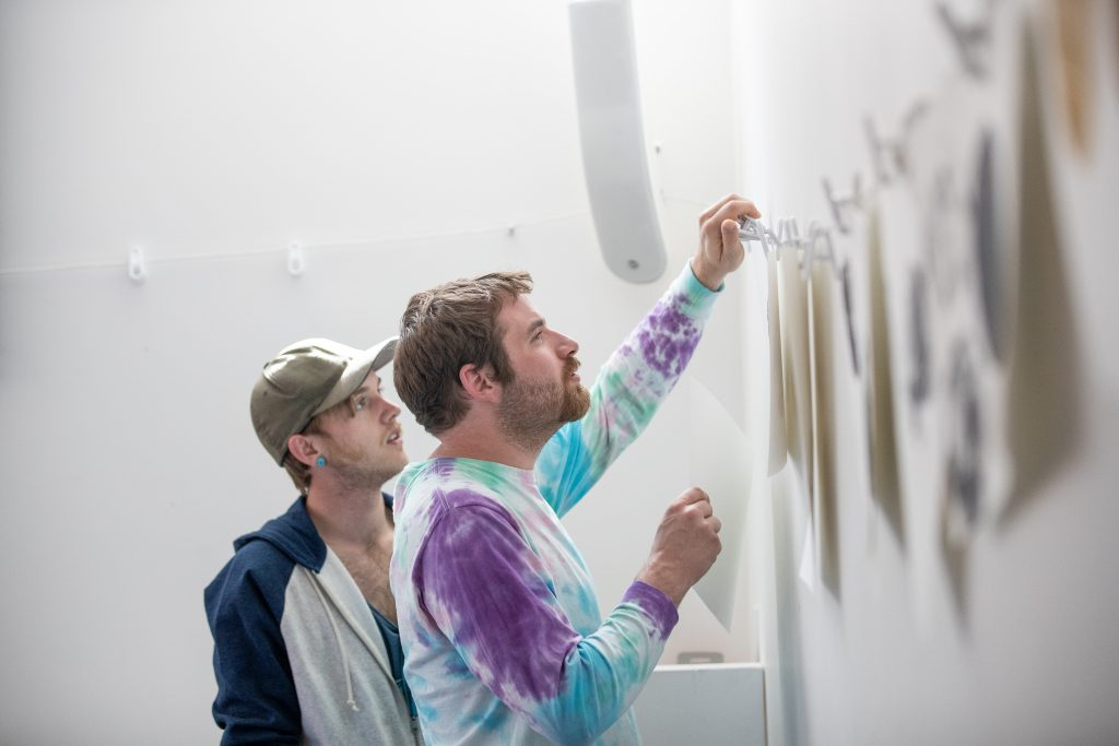 Ascendigo participant Zach, right, and his skills trainer, Richard Beutner, hang printmaking art on March 26 in the workshop space of the Aspen Art Museum.