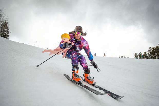 A skier carries a blow up doll down Aspen Highlands for closing day.