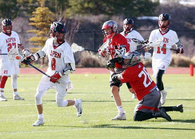 Aspen High School senior Garrett Hughes, left, looks for passing options in the boys lacrosse plays against Steamboat Springs on Wednesday, April 17, 2019, on the AHS turf. (Photo by Austin Colbert/The Aspen Times).