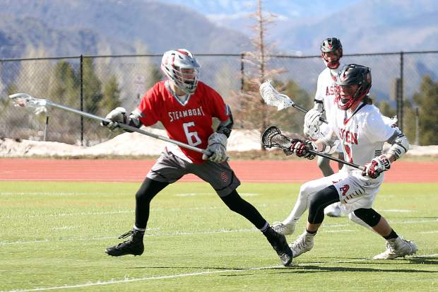 Steamboat Springs senior Jonathon Kaminski, left, avoids the Aspen defense in the boys lacrosse game on Wednesday, April 17, 2019, on the AHS turf. (Photo by Austin Colbert/The Aspen Times).