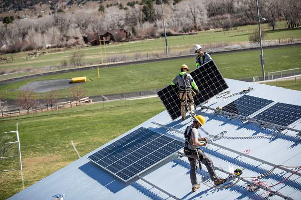 Sunsense Solar employees Kevin Lundy, Matt Greenlund and Cole Alexander install solar panels on the roof for the Habitat for Humanity Basalt Vista netzero project on April 19.