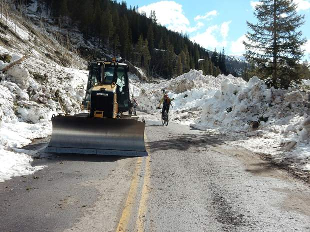 Cyclists make their way past CDOT equipment at the Green Mountain slide on Highway 82 east of Aspen on Thursday.
