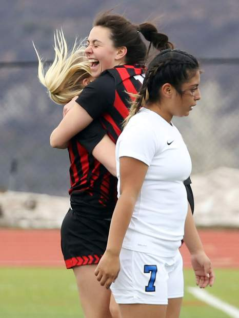 Aspen High School's Clara Maxwell, back right, hugs teammate Ellie Oates after Oates scored in the girls soccer game against Coal Ridge on Tuesday, April 16, 2019, on the AHS turf. The Skiers rolled to a 7-0 win to remain perfect since spring break. (photo by Austin Colbert/The Aspen Times).