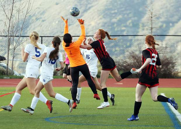 Aspen players converge around the Roaring Fork net on Thursday, April 25, 2019, on the AHS turf. Aspen won, 3-1. (Photo by Austin Colbert/The Aspen Times).