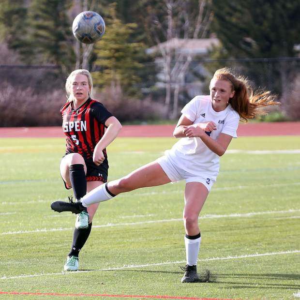 Aspen High School senior Margo McHugh, left, deflects the ball into the air during the girls soccer game against Roaring Fork on Thursday, April 25, 2019, on the AHS turf. Aspen won, 3-1. (Photo by Austin Colbert/The Aspen Times).