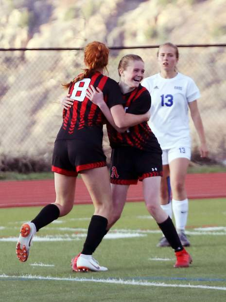 Aspen High School freshman Jenny Ellis, right, is hugged by junior Maeve McGuire after Ellis scored in the girls soccer game against Roaring Fork on Thursday, April 25, 2019, on the AHS turf. Aspen won, 3-1. (Photo by Austin Colbert/The Aspen Times).