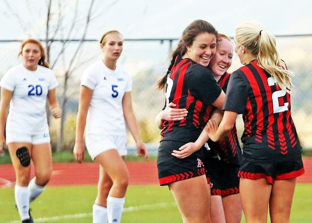 Aspen High School sophomore Kelley Francis, center in red, is hugged by seniors Clara Maxwell, left, and Ellie Oates after scoring her second goal in the girls soccer game against Roaring Fork on Thursday, April 25, 2019, on the AHS turf. Aspen won, 3-1, with Francis setting the program's single-season scoring mark with her 33rd goal of the season. (Photo by Austin Colbert/The Aspen Times).