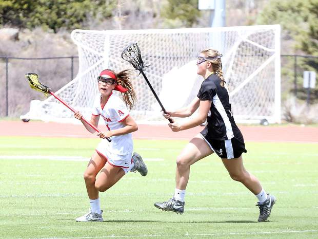 Aspen High School sophomore Kylie Kenny avoids a defender as the girls lacrosse team plays a game against Arapahoe on Saturday, April 27, 2019, on the AHS turf. (Photo by Austin Colbert/The Aspen Times).