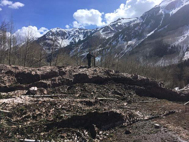 A man stands on the top of avalanche debris covering Maroon Creek Road last weekend.