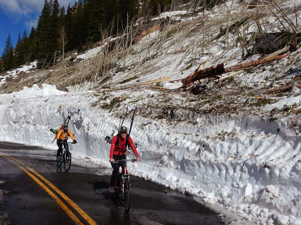 Karin Teague, front, and Greg Albrecht, ride Thursday through the debris of an avalanche that roared down from the top of Green Mountain, reached the valley floor and wiped out trees on the opposite side of Highway 82.