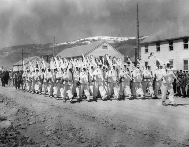 Tenth Mountain Division soldiers at Camp Hale, marching in uniform with their skis over their shoulders.