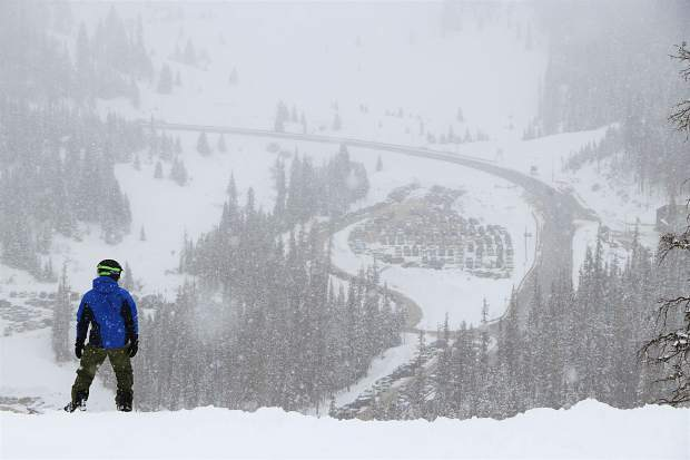 A snowboarder eyes the descent on the front-side of Arapahoe Basin Ski Area Tuesday morning in the midst of a May spring snow storm that dropped more than 6 inches of powder overnight Monday evening into Tuesday morning at the Summit County ski area at the Continental Divide.