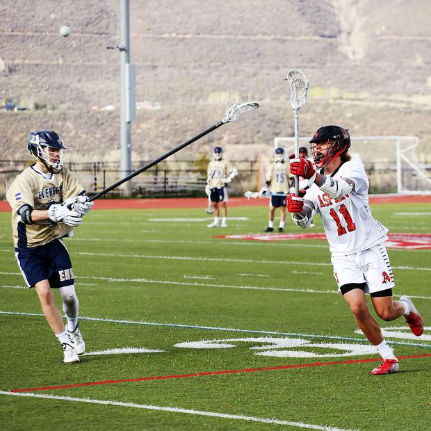 Aspen High School's Dillon Hendrickson, right, makes a pass in the boys lacrosse game against Evergreen in the first round of the 4A state playoffs on Tuesday, May 7, 2019, on the AHS turf. The Skiers lost, 10-5. (Photo by Austin Colbert/The Aspen Times)