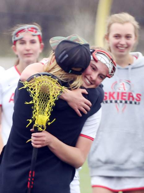 Aspen High School junior Charlotte Howie hugs girls lacrosse coach Amanda Trendell after they won against Air Academy on Saturday, May 11, 2019, on the AHS turf. (Photo by Austin Colbert/The Aspen Times)