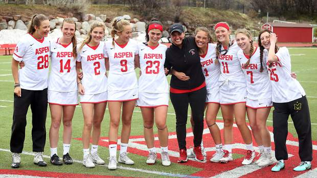 Seniors on the Aspen High School girls lacrosse team pose with athletic trainer Celty Fitterer after beating Air Academy on Saturday, May 11, 2019, on the AHS turf. (Photo by Austin Colbert/The Aspen Times)
