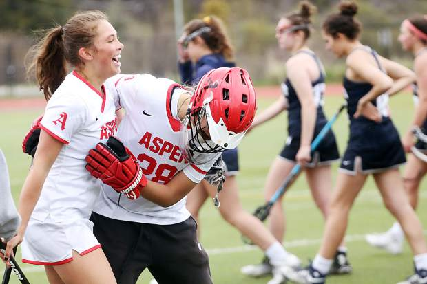 Aspen High School senior Tyler Greene, left, celebrates with senior goalie Livi Carr after the girls lacrosse team beat Air Academy in the second round of the playoffs on Saturday, May 11, 2019, on the AHS turf. (Photo by Austin Colbert/The Aspen Times)