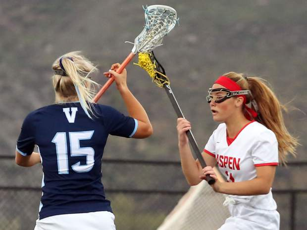 Aspen High School senior Juna Rettig, right, goes on the attack in the girls lacrosse game against Valor Christian in the state quarterfinals on Wednesday, May 15, 2019, on the AHS turf. (Photo by Austin Colbert/The Aspen Times)