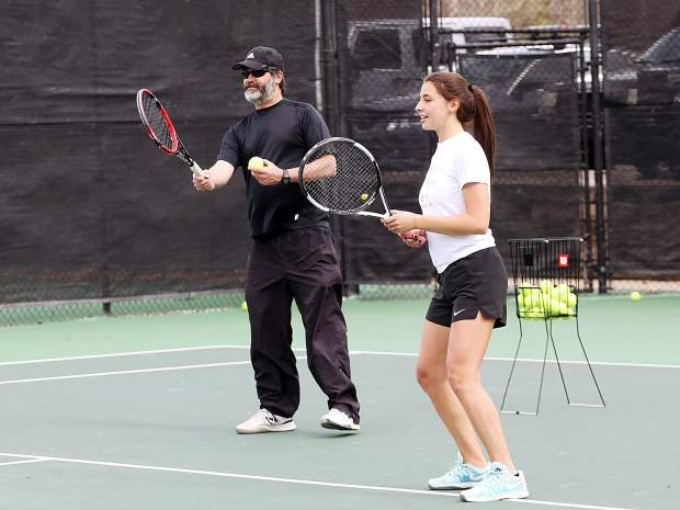 Junior Virginia Tassi, right, waits as coach Steve Sand prepares to put the ball in play during practice on Monday, May 6, 2019, at Snowmass Club, only days before the Aspen High School girls tennis team heads to the Class 3A state tennis championships, which get underway Thursday in Greeley. (Photo by Austin Colbert/The Aspen Times)