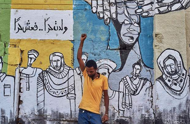 Galal Yousif, photographed by Ahmed Awad, with one of his murals.